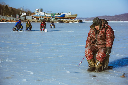 natural ice pastime: fisherman catches fish in the winter, Russia, Vladivostok