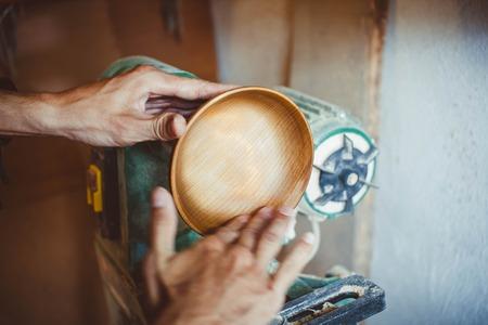 polished wood: Wood turners using sandpaper polished wood on a lathe Stock Photo