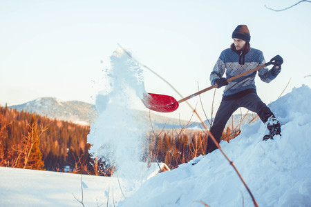 Happy young woman shovelling snow against blue sky Stock Photo
