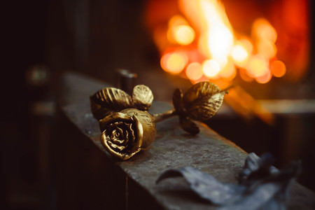 A metal forged rose lies on the pier in the smithy