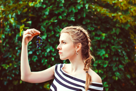 Woman in the summer garden in a dress eating a berry Stock Photo