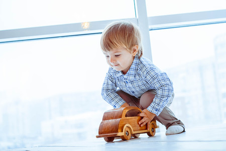 A boy is playing with toy cars near the window Imagens