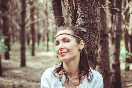 A young woman stands between trees in a forest Stock Photo