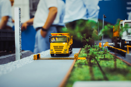 dumptruck: Yellow toy dump truck is isolated on the road Stock Photo