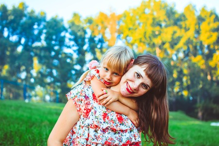 Cute young daughter on a piggy back ride with her mother. Looking at camera. Stock Photo