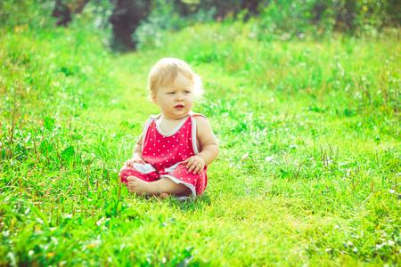 草の上に座っているドレスの少女