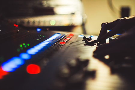 The hands of the sound engineer on the mixing console