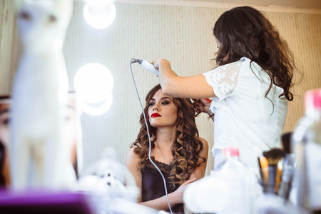 Hair stylist making ringlets to brunette woman. Hairdresser working with beautiful woman hair in hairdressing salon.
