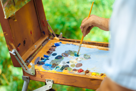 Close up view of artist painting picture outdoors 版權商用圖片