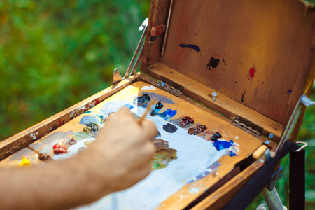 autumn colouring: Close up view of artist painting picture outdoors Stock Photo