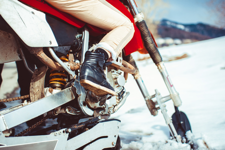 Feet on the bottom of the motorcycle in winter Stock Photo