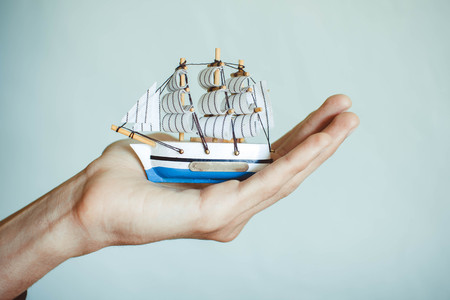 toy ship in the hands in the room on a white background Stock Photo