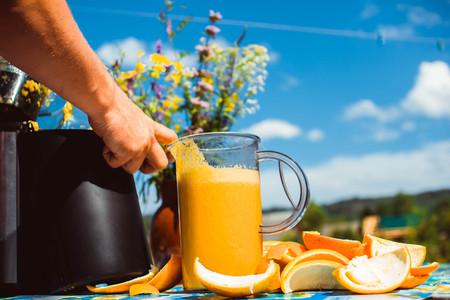 Man preparing fresh orange juice. Fruits in background on wooden desk Stock Photo