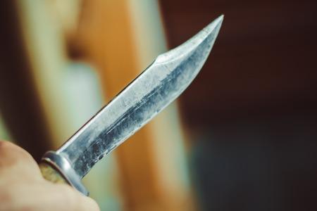 Male hand holding knife on black background.