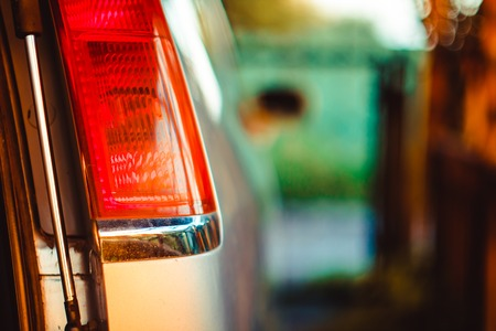 Modern blue car tail light in wet rain drop. Red modern car back light Stock Photo
