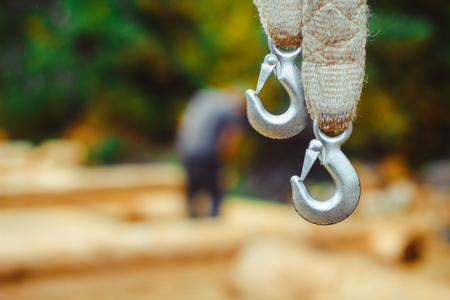 heavy industry: End of swinging rope hang on metal construction in a park. Rough rope end in metal circles and safety snap hook Stock Photo