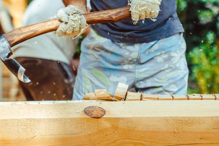 Handen van een sterke man hout splijten met een bijl, focus ligt op de bijl, bevriezen motie op het moment dat het splitsen