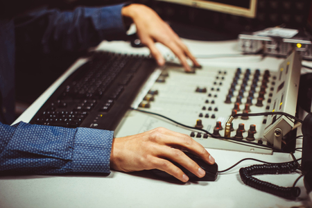 Professional audio mixing console with faders and adjusting knobs - radio