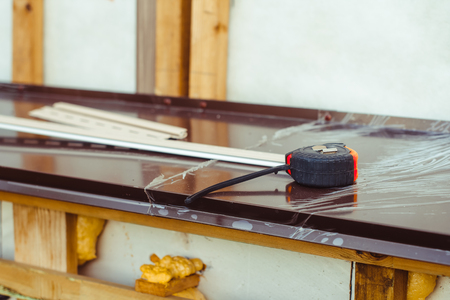 The Construction Tape Measure Rests On The Windowsill Outside The House  Photo