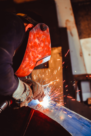 worker welding metal with sparks and smoke in the helmet