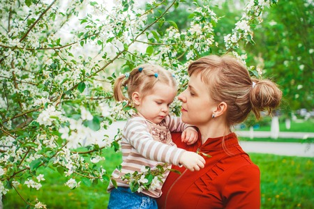 Close up portrait of a joyful mother and daughter relaxing together in a beautiful spring field of grass and flowers, hugging and enjoying a sunny holiday outdoors. Family love and lifestyle. Stock Photo