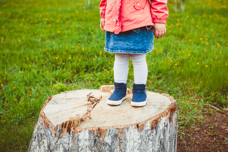 children s feet: Baby bare feet on the stump with natural wood background. Stock Photo