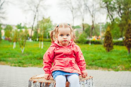 little girl sitting on a stump in the summer garden