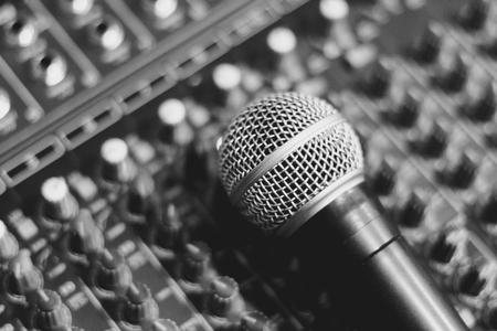 the microphone rests on an audio mixer Stock Photo