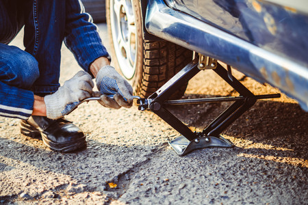Jacking up a car to change a tyre after a roadside puncture with the hydraulic jack inserted under the bodywork raising the vehicle and the spare wheel balanced on the side. Stock Photo