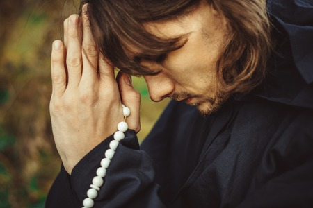 a monk in a black robe praying in the woods on his knees Stock Photo