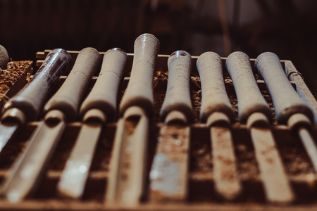Old used wood lathe chisels selection on the dark wooden table, selective focus