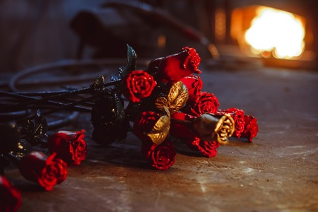 Forged metal rose lying on the pier in the smithy behind the fire