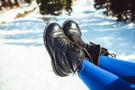 Legs of a woman in shoes at a winter resort