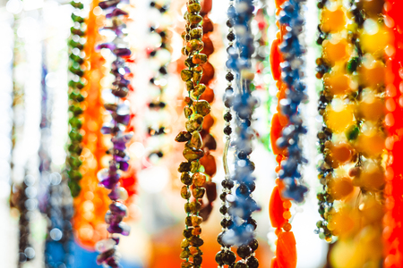 Colorful bijouterie and necklaces with beads hanging for sale in a shop