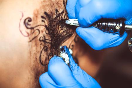 Tattooer showing process of making a tattoo hands holding a tattoo machine