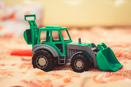 A toy tractor in the nursery on the floor