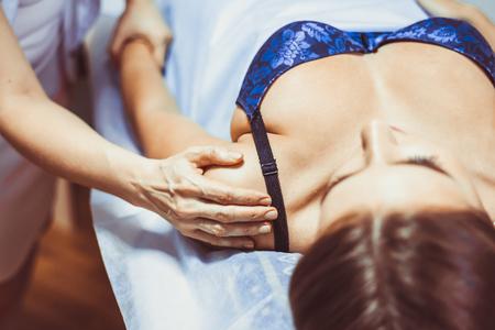 Close up of massager hands massage shoulder