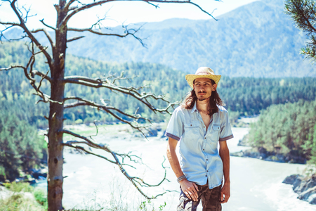 A young man in a cowboy hat against the background of a mountain river
