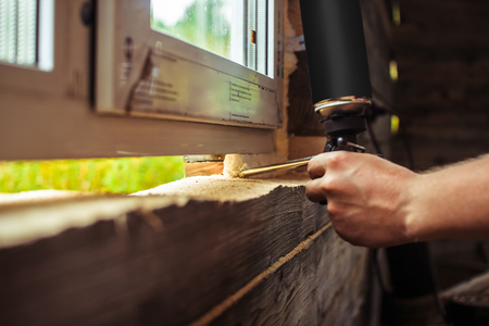 Applying polyurethane foam. Detailed view on process of installing a polyvinyl window. Working for a construction company.
