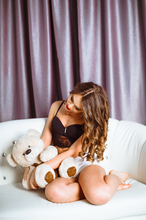 Cheerful smiling girl sitting on the couch, holding the bears toys.