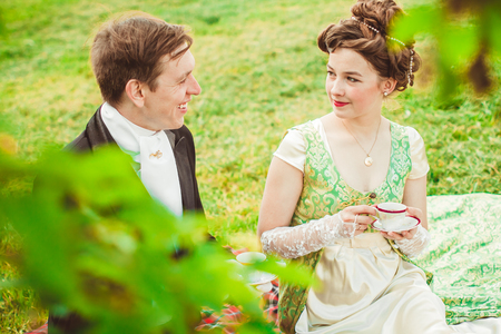 Beautiful girl in the lush dress drinks tea. Photoshoot in the Rococo style. Historical Portrait. Stock Photo
