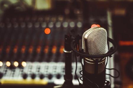 Professional condenser studio microphone over the musician blurred background and audio mixer, Musical instrument Concept. Foto de archivo
