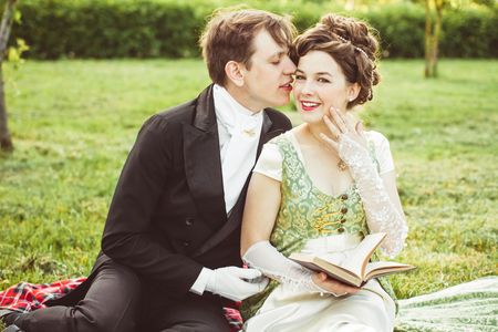 couple in period costume reading a book in nature