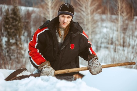 the young man relaxes before a shovel of snow on the roof of the cottage Stock Photo