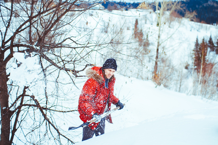 a young man shovelling snow on blue sky background Stock Photo