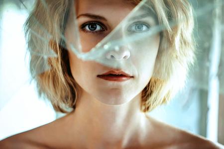 Woman looking through dirty broken glass closeup