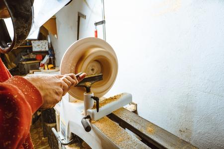 el trabajador gira la madera en un torno en su taller Foto de archivo