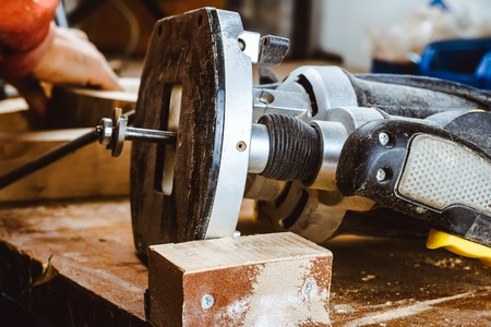 Processing of a furniture part by a machine for polishing a tree. the grinding machine on a board, selective focus. Process of processing the edges of a furniture product in side view