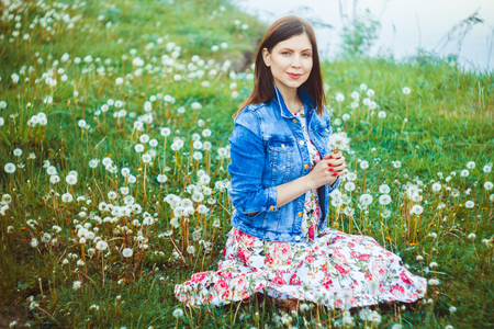 Beautiful young woman among dandelions and grass Stockfoto