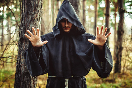 the black monk pointing his finger in the woods Stock Photo